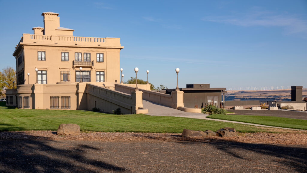Maryhill Museum of Art, with the stone bulding on the left side of the photo and a green lawn in the foreground