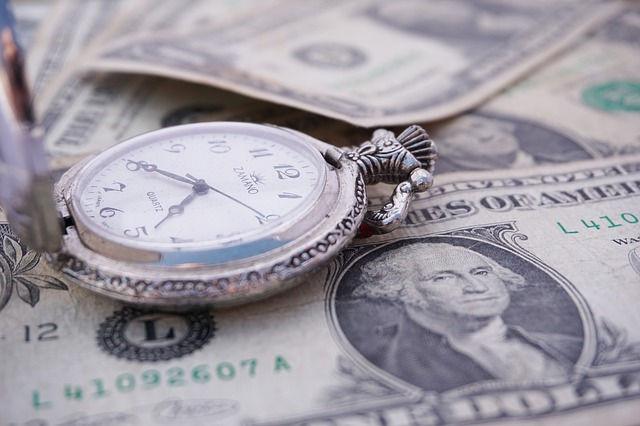 A pocket watch on dollar bills.
