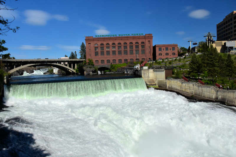 the beautiful spokane falls is right in the center of town in spokane washington with buildings and a bridge