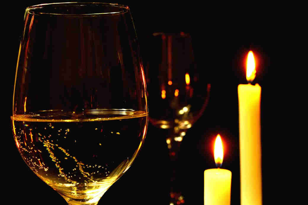 A wine glass with candles in the background.