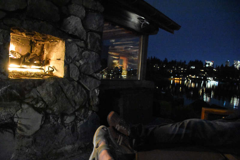 Relaxing next to the outdoor fireplace at the lakeside cabin near Seattle.