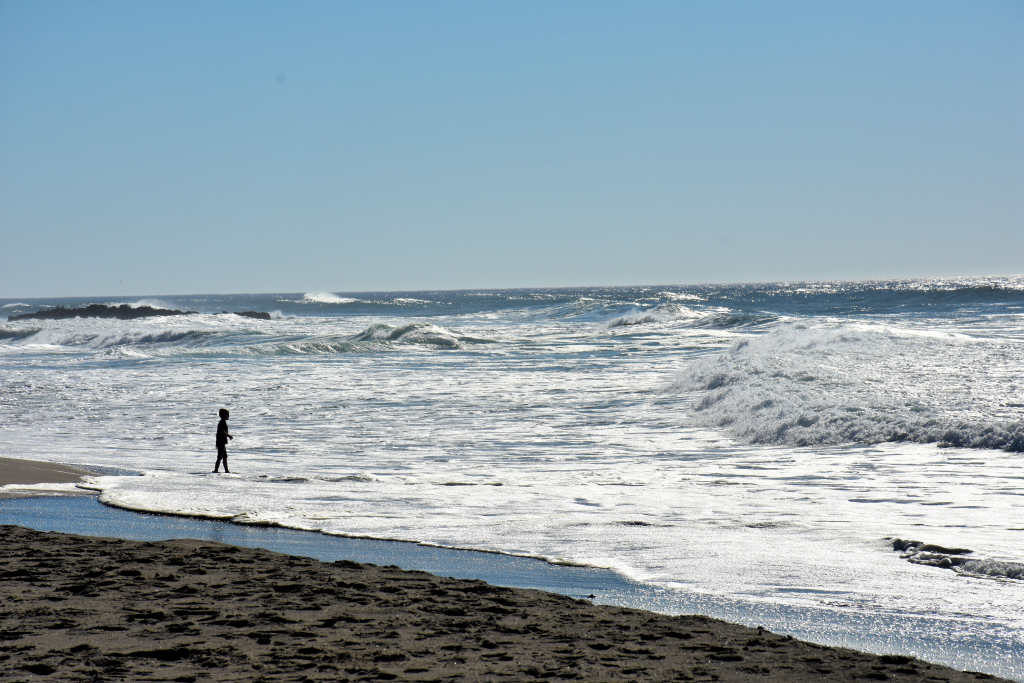 A boy standing in the surf in Lincoln City, Oregon.