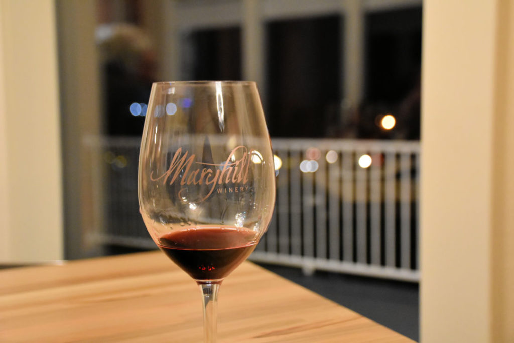 glass of red wine from maryhill winery sitting on a wood table at night