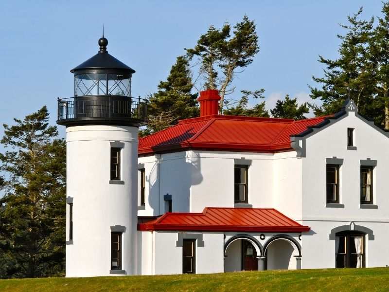 A white, red, and black detailed lighthouse with a large cottage attached with grass and trees.