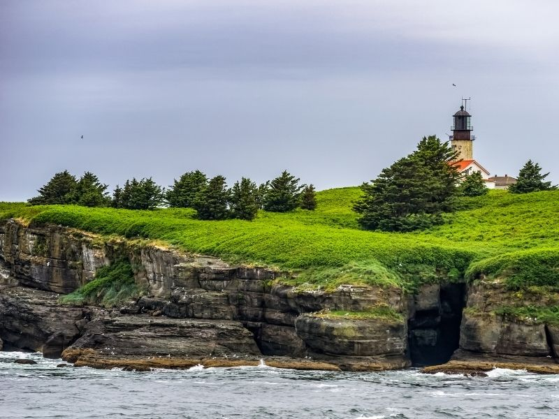 Sea cliffs covered in green grass and trees on an overcast day with a small lighthouse on the cliff edge.