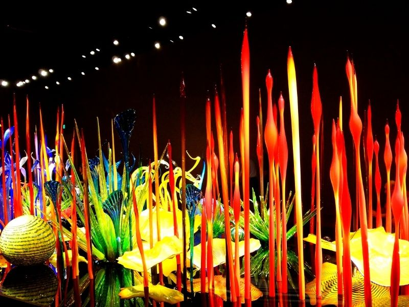 Red and yellow and green blown glass sculptures forming what looks to be a garden. Glass art by Dale Chihuly shown in a museum in Seattle in winter.