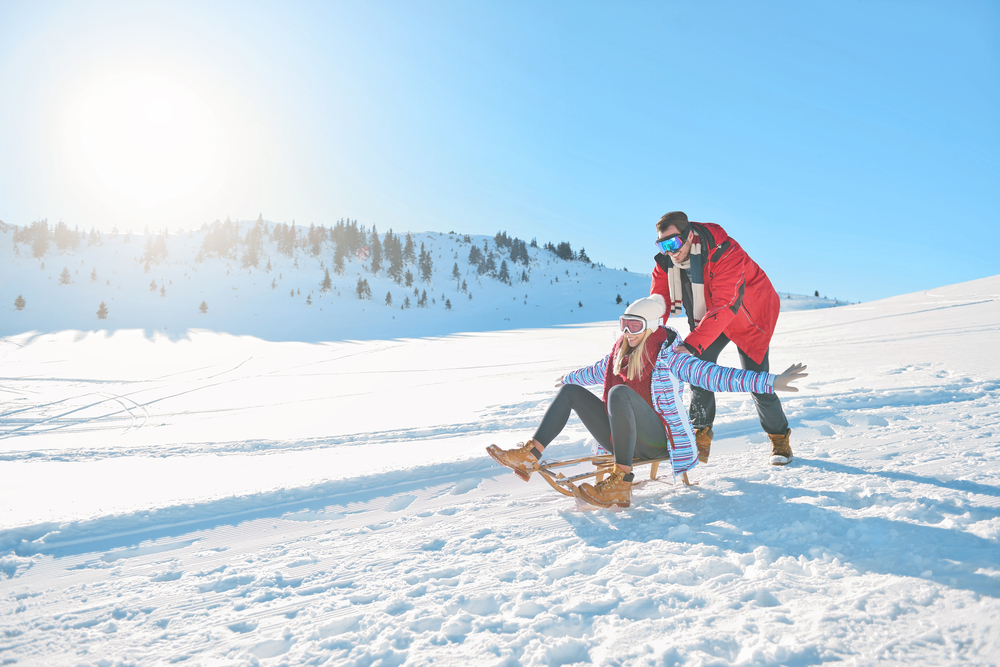 A couple enjoying a sled ride on a wooden sledge with the woman lifting her hands up and the man pushing the sledge