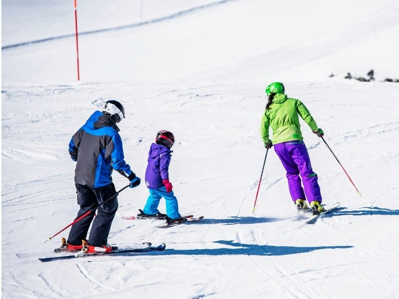 Mother, father, and child learning to ski on a ski hill in Leavenworth Washington in winter.