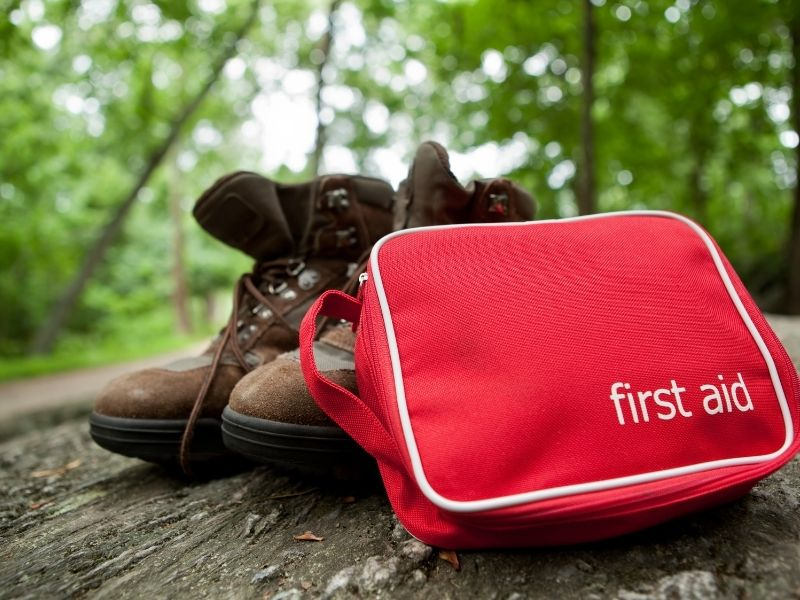 """A pair of hiking boots with no one wearing them and a medium-size red zippable cloth bag which reads """"first aid"""", shown with a forest background. Don't forget safety when packing for Seattle hikes!"""