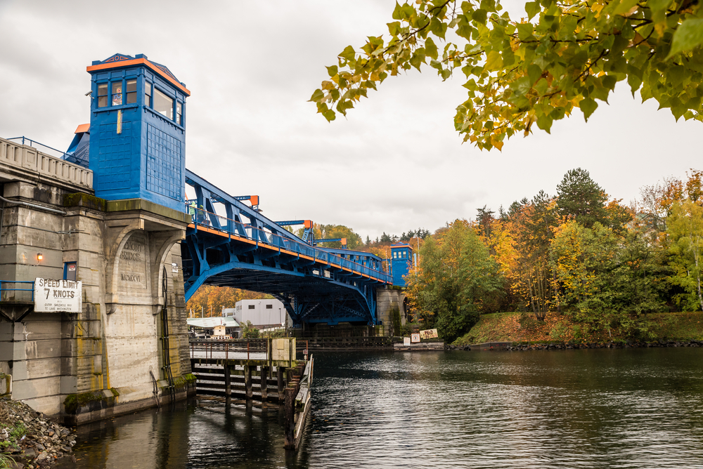 Colorful blue and orange drawbridge over a Seattle waterway with fall foliage trees in the background on a gray sky day.