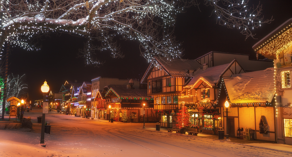Snowy Leavenworth winter street with traditional Bavarian style architecture and Christmas lights and an orange glow to the street.