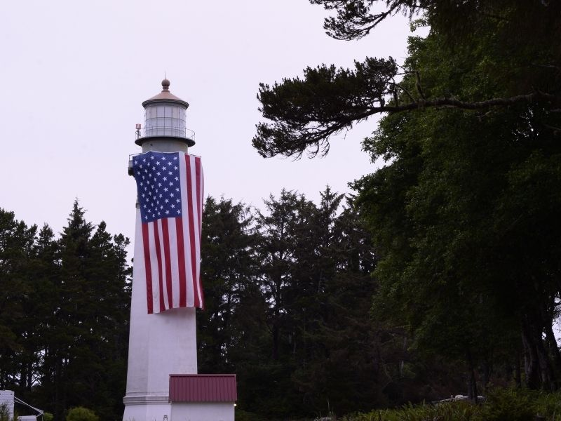 A white lighthouse with a giant American flag hanging on it, amidst trees on an overcast, cloudy day.