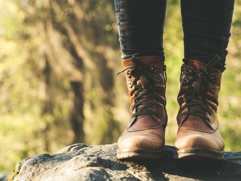 A close up view of brown hiking boots with jeans tucked into them as a woman stands on a rock. Hiking boots are key for what to pack for Seattle if you hike.