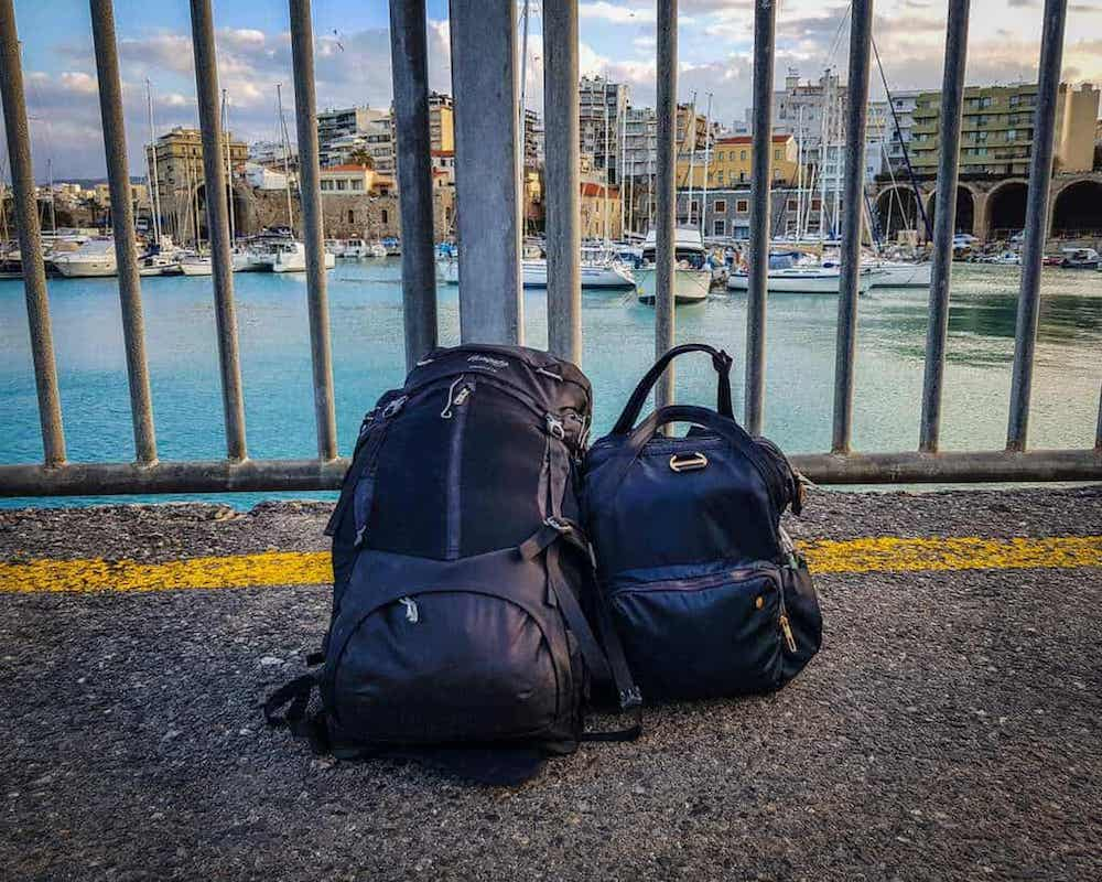 Two backpacks, one smaller and one larger, with zipper details with a view of the harbor behind them. Don't forget a secure daybag when packing for Seattle!