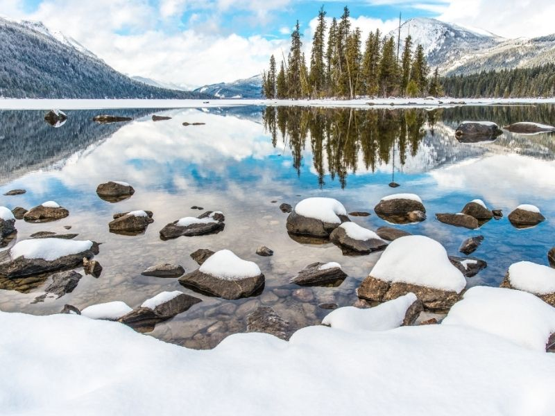Snow-covered landscape and rocks with the lake still unfrozen in Lake Wenatchee State Park, a popular place for snow play near Leavenworth in winter