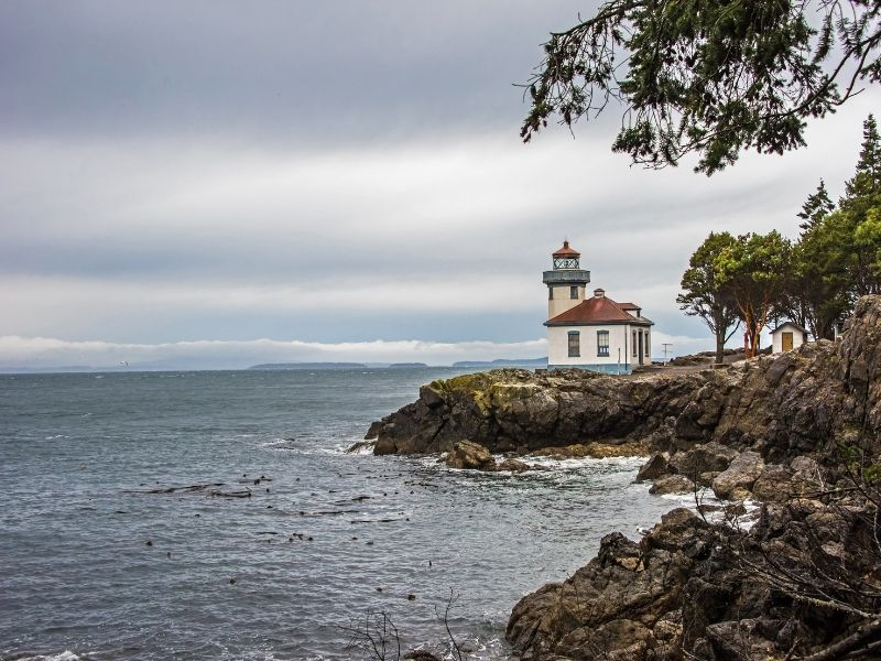 Overcast day with the small lighthouse on San Juan Island, Lime Kiln, with white walls and a red roof, and trees and cliffs next to the gray ocean surf.