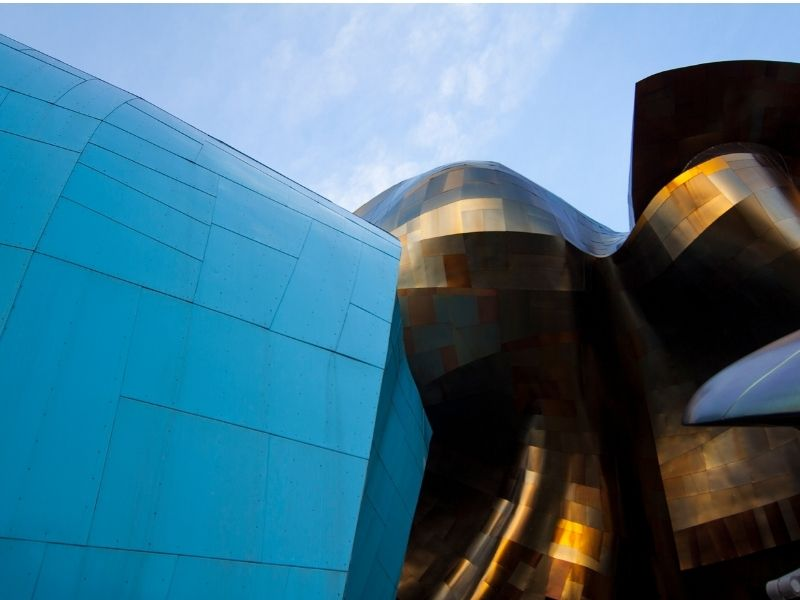 Close up of modernist architecture at the Museum of Popular Culture: one side is curved and teal, the other is bronze and curved architectural pieces in traditional Frank Gehry style.
