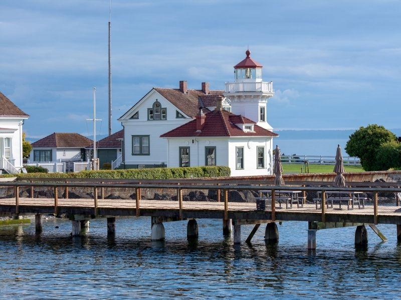 The sea and a pier in the foreground with the lighthouse behind it, with white walls and red roof and detailing, on a cloudy day in Mukilteo.