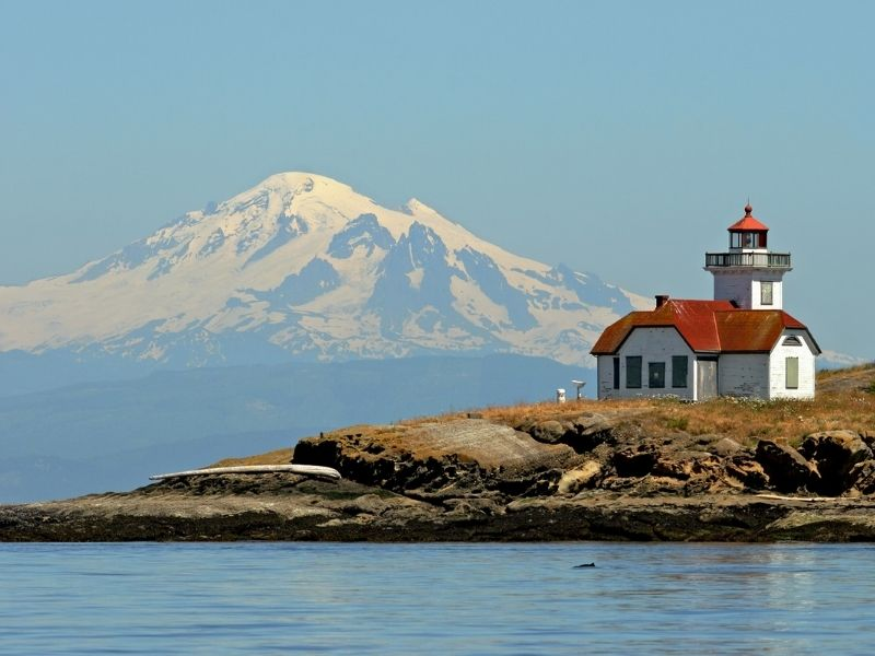 A small white and red-roofed lighthouse on a small rocky island with a snow-capped mountain off in the distance.