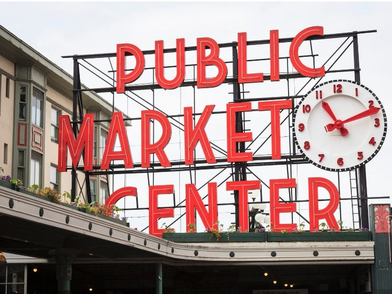 "Vintage lettering which reads ""Public Market center"" in all-caps red font with a clock, also white and red, at the entrance to Pike Place Market, one of the top things to do in Seattle for foodies."