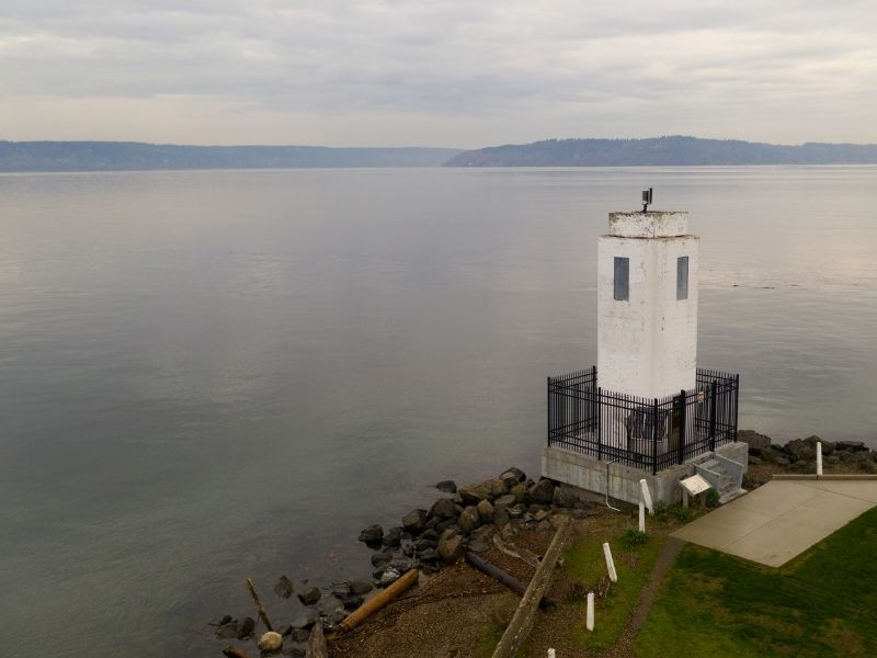 A unique rectangular lighthouse that is all white with a black gate around it on the edge of the water on a cloudy day.