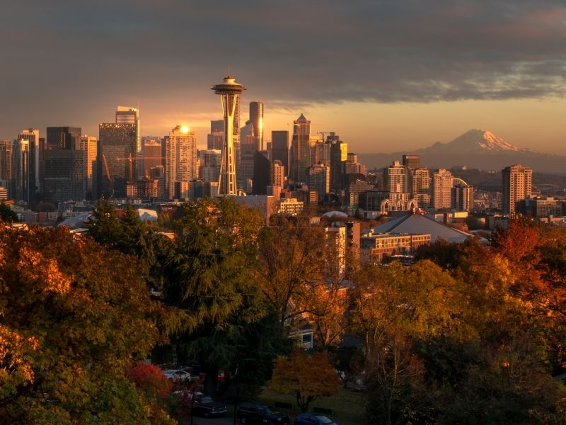 A view of Seattle's downtown, including the Space Needle and Mount Rainier, on a cloudy fall day at sunset with trees showing their fall colorsor red and orange.