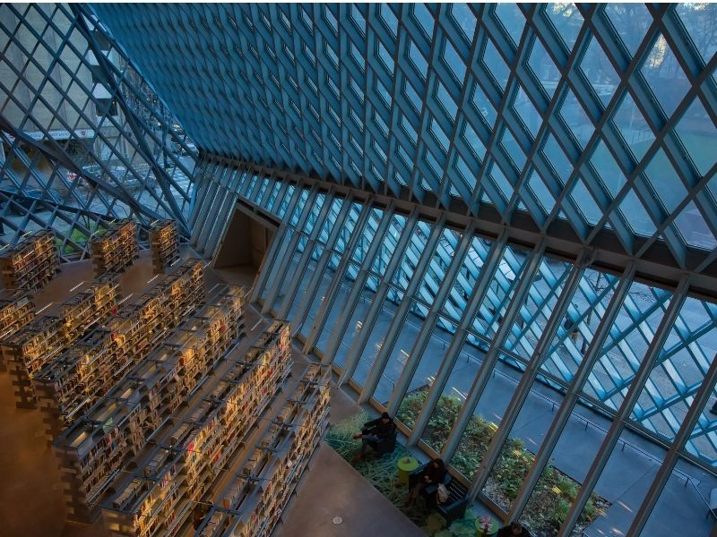 Photo from a higher floor of the Seattle Public Library showing the glass and steel diamond-pattern construction as well as shelves upon shelves of books on display.