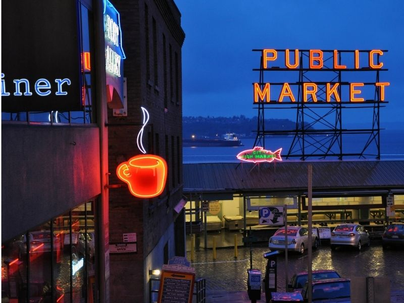 "Night view of Pike Place Market with neon sign saying ""Public Market"" and a neon sign of a cup of coffee."