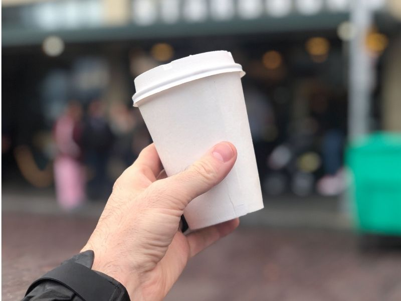 Hand holding a white coffee cup with a blurred out background.
