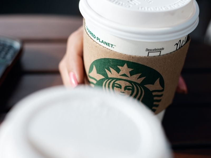 Two Starbucks cups cheersing with focus on the logo on the paper cup.