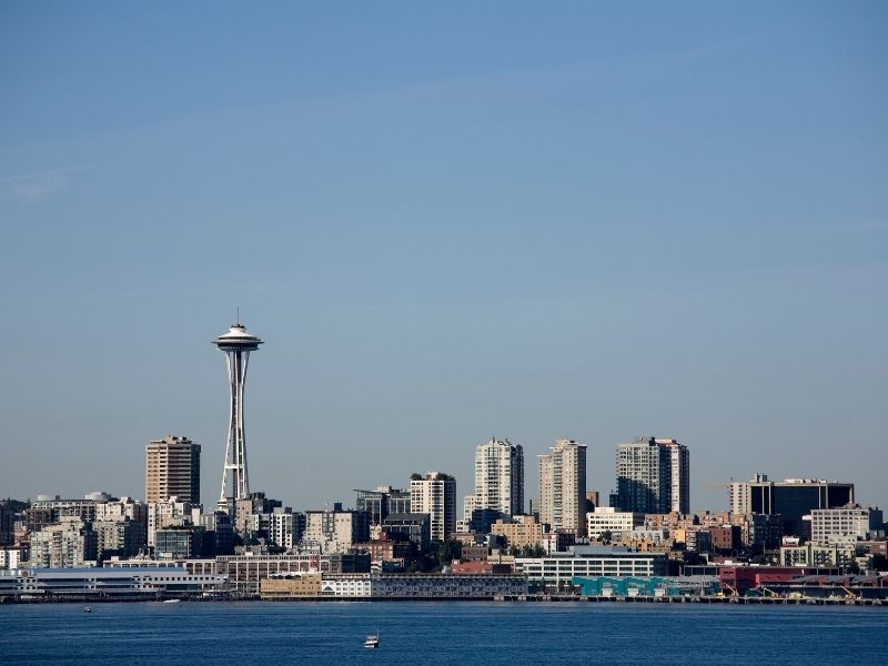 A view of the Seattle skyline, including the Space Needle, as seen from a boat out on the Puget Sound, on a cloudless blue sky summer day.