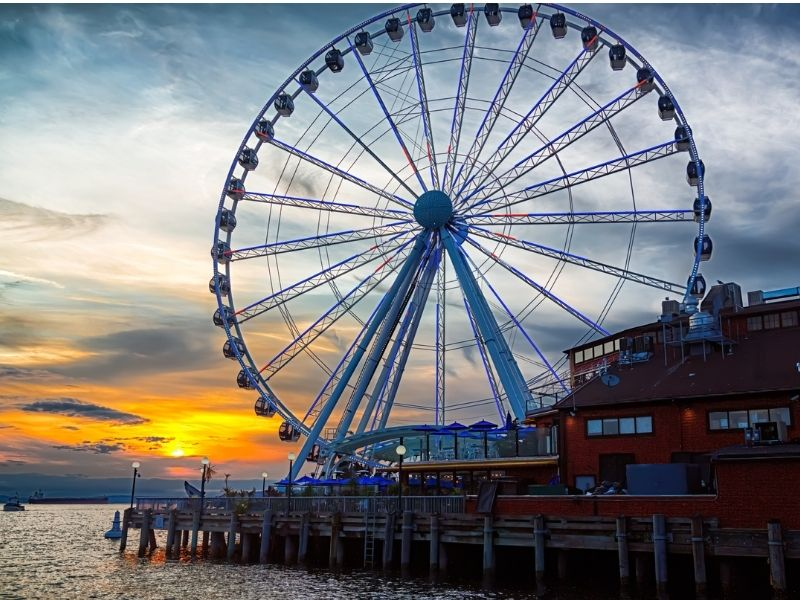 The Seattle Great Wheel giant Ferris Wheel on the pier at sunset with a cloudy sky featuring brilliant colors.