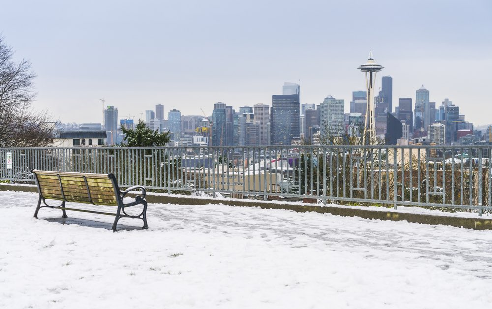 A view of a bench overlooking the Seattle skyline, including the Space Needle, while there is a small layer of snow on the ground next to the bench on a Seattle winter day.