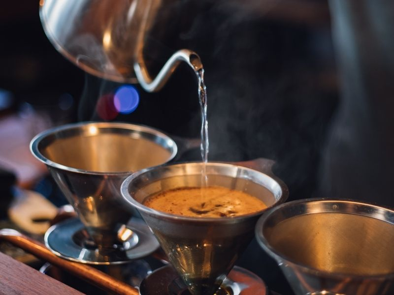 Three cups of pourover coffee being prepared at a hip third wave coffee shop.