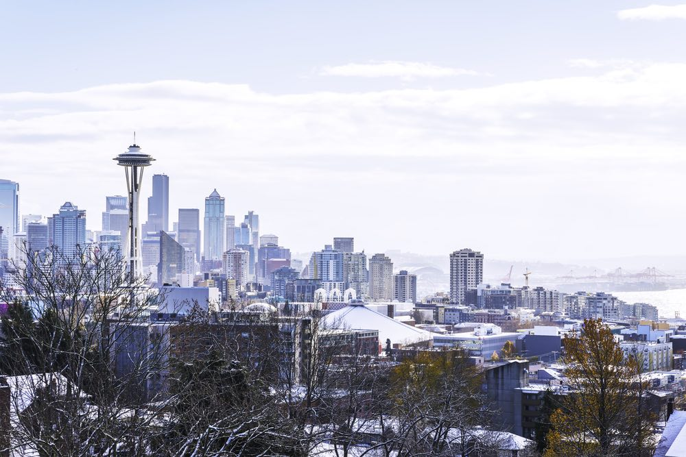 Winter in Seattle landscape after a snowfall, showing snow blanketing hte trees and buildings on an overcast day.