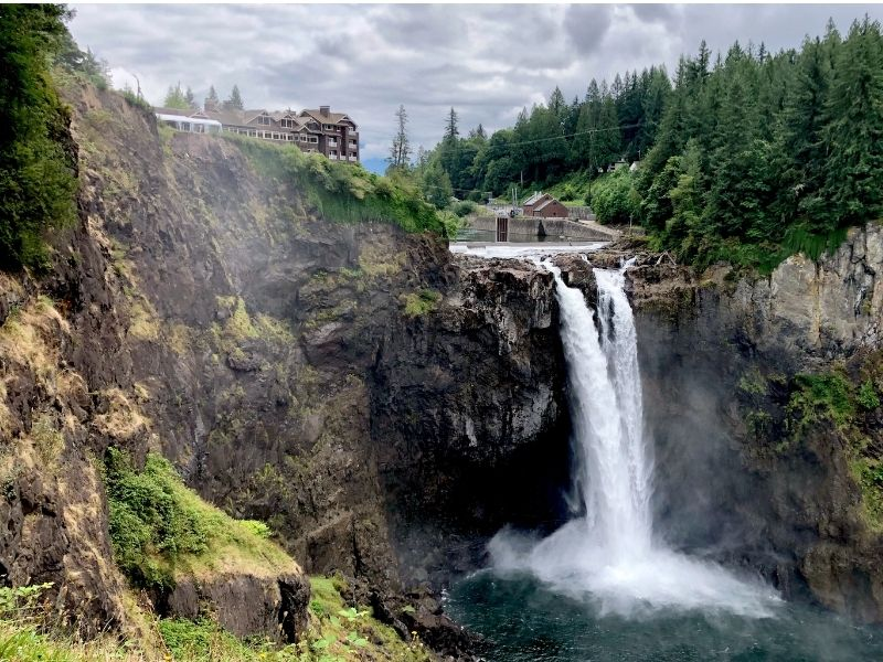 View of Snoqualmie Falls waterfall on a cloudy day with water thundering over into a turquoise pool below and pine trees framing the waterfall.