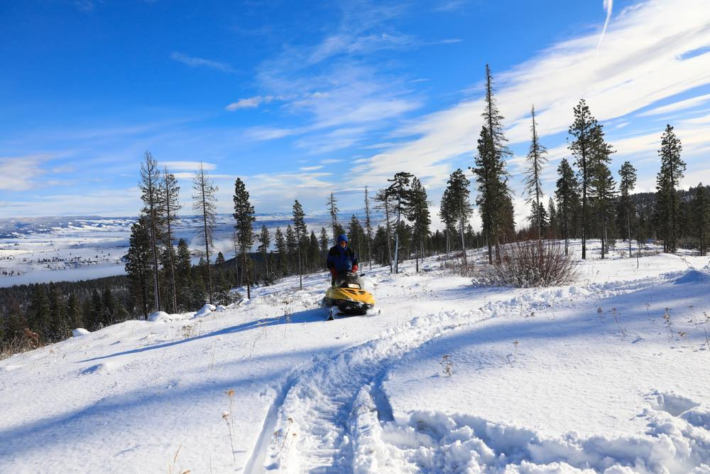 A  man on a yellow snowmobile in the Cascade mountains on a sunny day with lots of snow