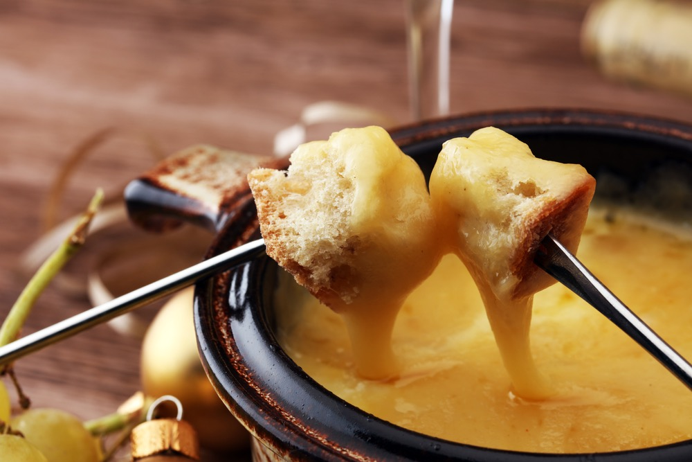 Two cubes of bread being dunked in hot melted cheese in a fondue pot using fondue forks.