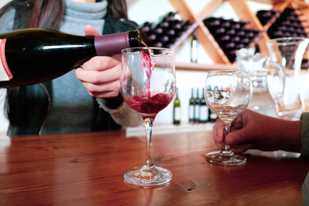 Tasting room sommelier pouring a glass of red wine for a client visiting the establishment.