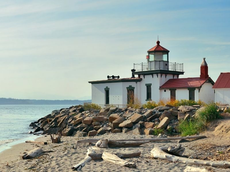 A sandy shore with some driftwood and large rocks with a lighthouse with white walls, and dark green and red detailing on it.