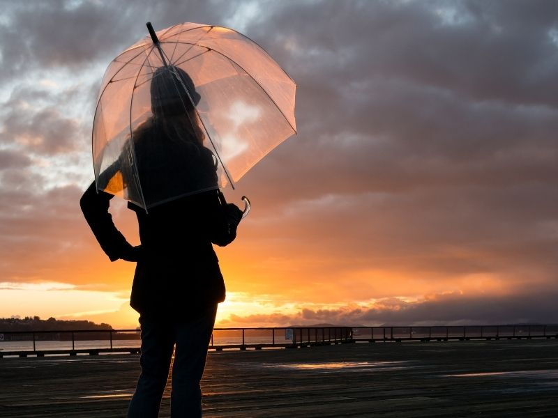 A woman carrying a clear umbrella on a rainy, overcast day in Seattle while the sun sets in the distance: an umbrella is a must-have Seattle packing list item!