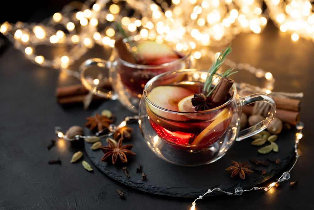 Two cups of mulled wine with spices used in making mulled wine around them with Christmas lights out of focus in background.