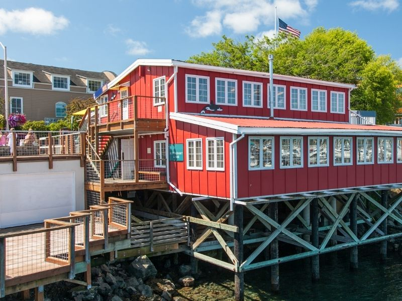 A bright red wooden building on the pier in Friday Harbor, San Juan with an American flag flying.
