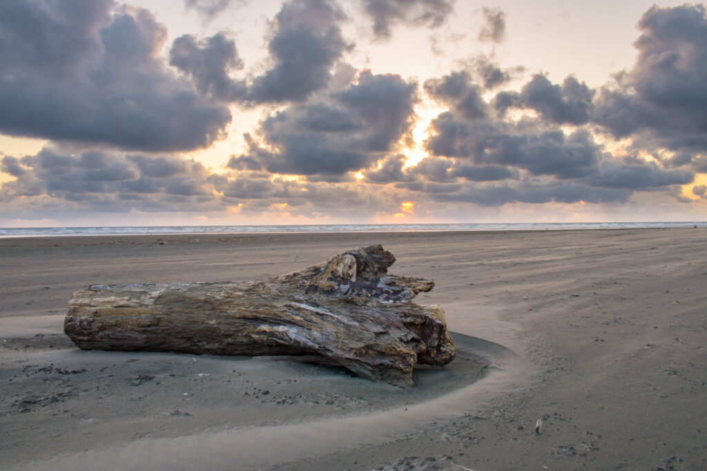 empty seabrook beach washington with a log on the sand in the foreground and a sunset beginning in the background