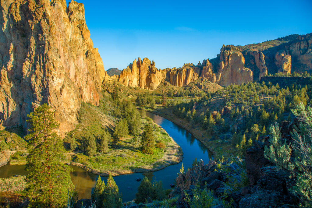 smith rock oregon with a river in the center of the photo, taken near golden hour