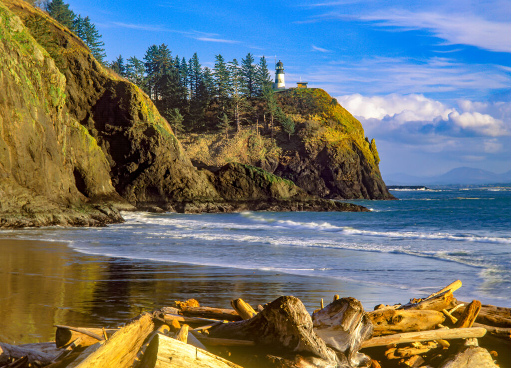 beach at cape disappointment, home to some of the best washington state beaches. a lighthouse is visible on a cliff in the distance