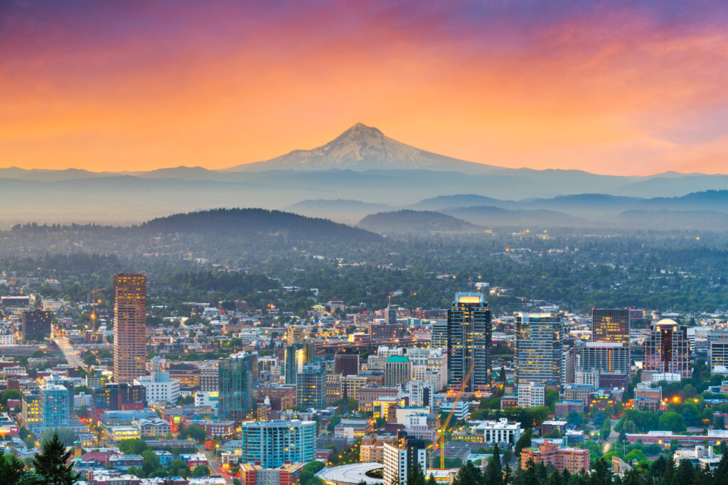 skyline of portland oregon at sunset with mount hood visible in the distance