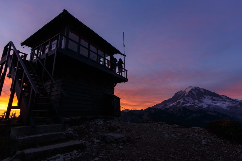 tolmie peak lookout stand in mount rainier national park at sunset. serveral people are standing nearby taking photos