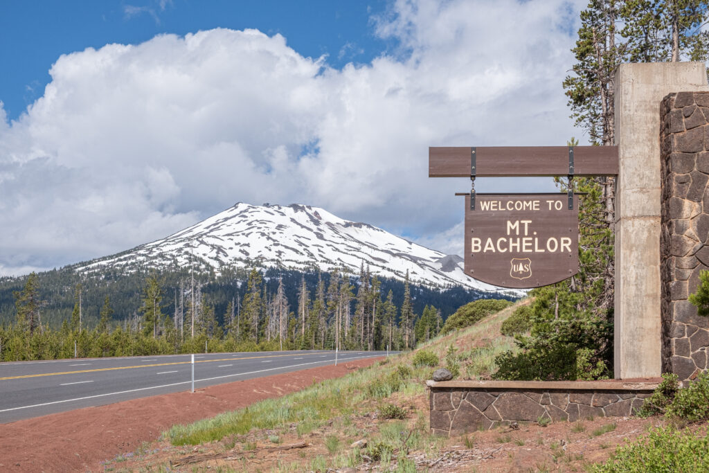 "view of snowcapped mount bachelor with a wood sign saying ""welcome to mt bachelor"" in the foreground"