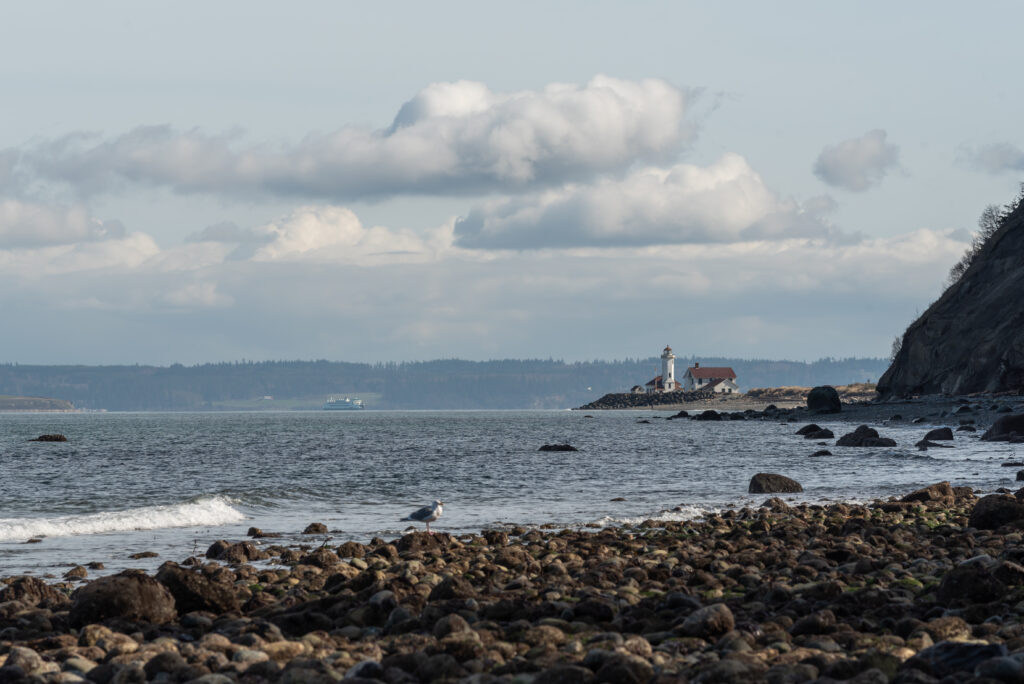 rocky beach with a lighthouse in the distance at fort worden state park, one of the best weekend getaways from seattle washington